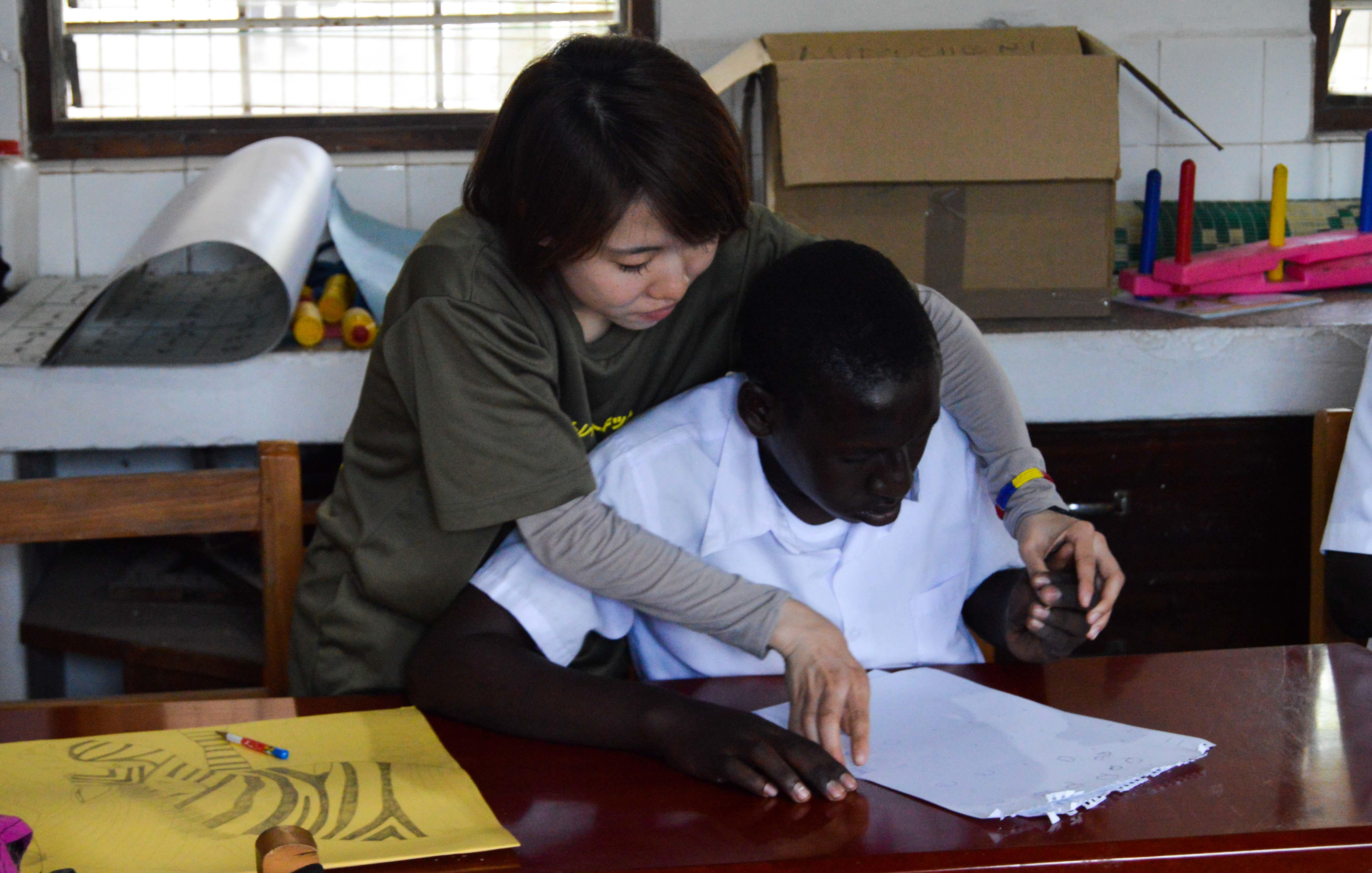 Projects Abroad experienced intern is pictured helping a boy learn to draw whilst on her medical occupational therapy internship in Tanzania.